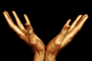 Two male hands in gold paint isolated