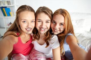happy friends or teen girls taking selfie at home