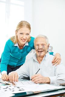 Familie mit Senior löst Sudoku