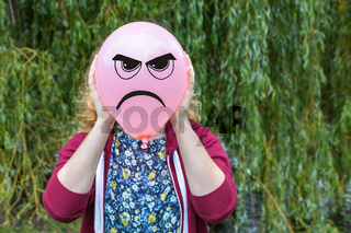 Girl holding balloon with angry face
