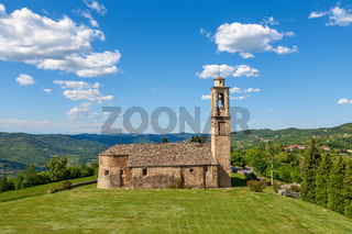 Old church on green lawn in Italy.