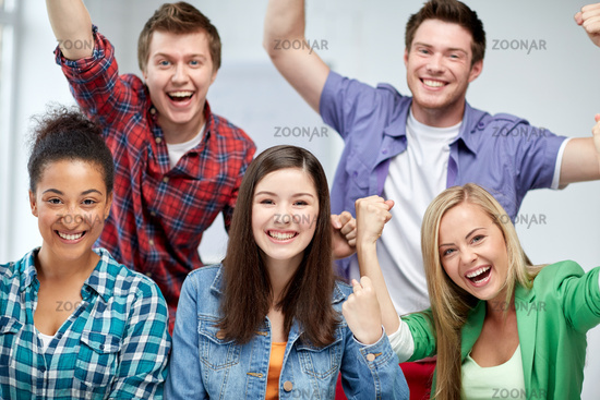 group of happy students making triumph gesture