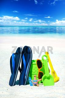 Mit Strandpielzeug und Flips Flops am Badestrand