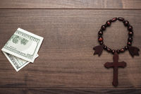 wooden cross and money on brown table background