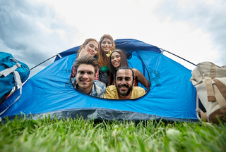 happy friends with backpacks in tent at camping