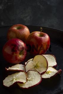 Stilleben mit frischen Äpfeln und mehreren getrockneten Apfelscheiben