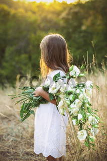 Little girl in a meadow with white wild summer flowers