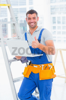 Smiling handyman with laptop gesturing thumbs up in office