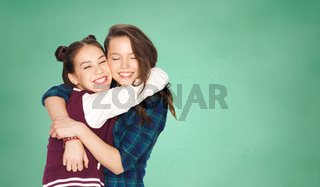 happy teenage girls hugging over green board