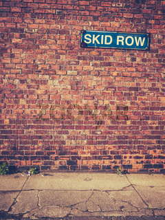 Skid Row Sign On Brick Wall