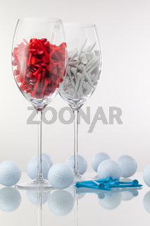 Two glasses of wine and golf equipments