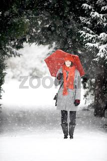 Frau im Schnee mit rotem Schirm