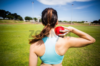 Rear view of female athlete preparing to throw shot put ball