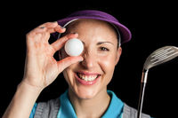 Golf player posing with a golf club and golf ball