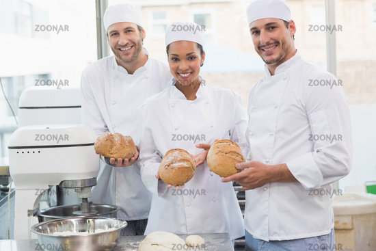 Team of bakers smiling at camera holding bread