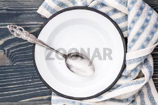 Empty White Enamel Plate Wrapped with Napkin