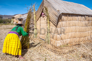 Unrecognizable woman in national costume Indian Uros knits a sheaf. Uros - Floating Islands, Titicaca, Peru