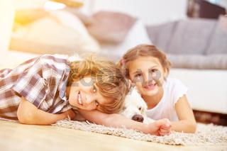 Zwei Kinder spielen mit dem Hund zu Hause