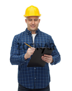 smiling male builder in helmet with clipboard