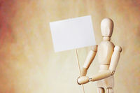 Wooden puppet holding blank white poster in its hands. Conceptual image about claims