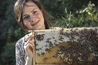 Imkerin hält Wabe voller Bienen