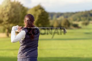 Frau schlägt beim Golf auf das Fairway