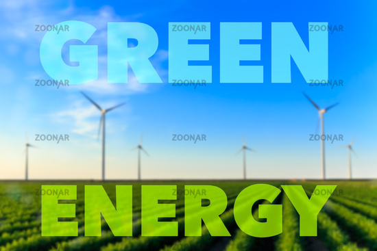 Blurred image of windmills at sunset at a field of crops. Text green energy.