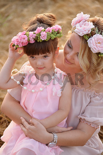 Mother and daughter hugging on her head a garland of roses, soft image
