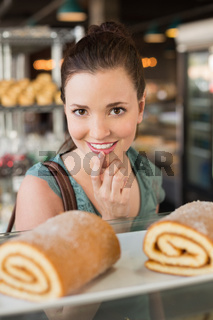 Pretty brunette looking at swiss roll