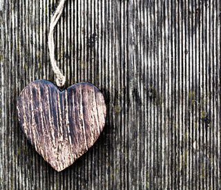 A wooden vintage heart on grunge wood planks. Symbol of love
