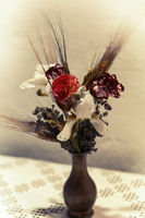 Vase of dried and fresh flowers in a an old faded style.