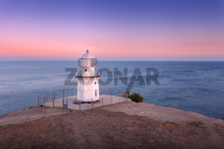 Beautiful white lighthouse on the ocean coastline at sunset. Landscape
