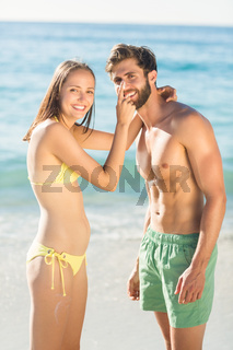 Happy couple in swimsuit looking at camera
