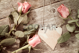 Three roses and hanging paper heart