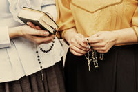 Detail of two womens hands with bible and rosary beads wearing 19th century clothing.