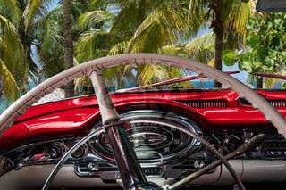 Kuba Innenansicht eines roten Oldtimers mit Palmen und Blick auf das Meer