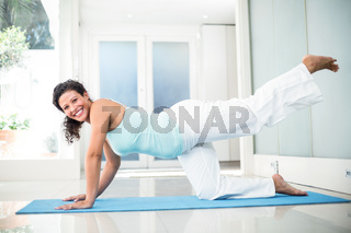Smiling pregnant woman performing yoga on mat