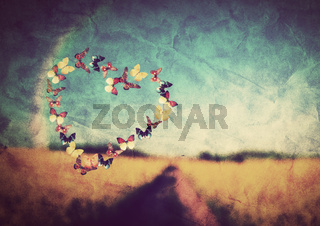 Heart shape made of colorful butterflies on vintage field background. Love