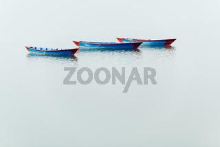 Three blue boats on Phewa Lake in Pokhara
