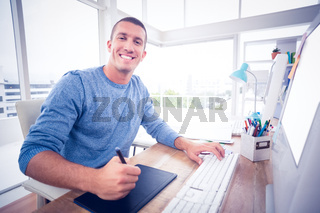 Young creative businessman drawing on graphic tablet