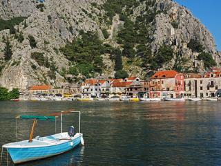 Blick auf die Stadt Omis in Kroatien mit Fischerboot im Vordergrund