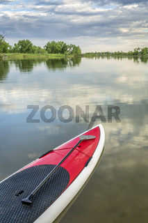 stand up paddleboard on calm lake