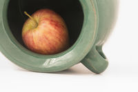 close up view of a red apple inside the greenish earthen jar