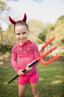 Portrait of cute girl smiling and pretending to be a devil