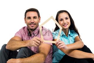 Smiling couple sitting on floor holding house shape