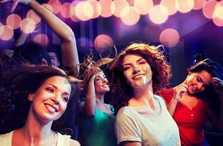 smiling friends dancing in club