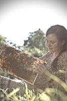 Junge Imkerin mit einer Wabe voller Bienen