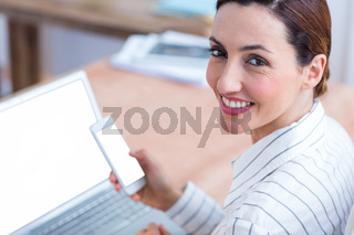 Brunette businesswoman smiling using laptop and her mobile