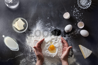 Woman's hands knead dough on table with flour