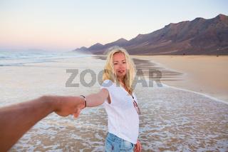 Romantic couple holding hands on beach.